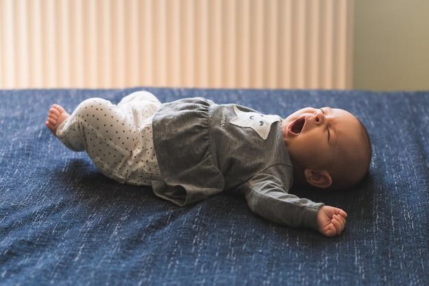 Baby auf blauer hintergrunddeckenahaufnahme