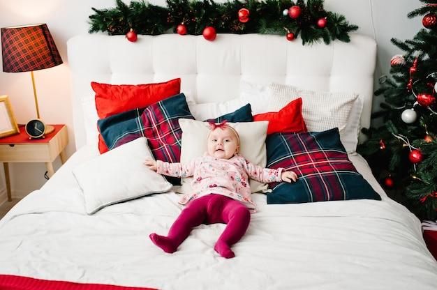 Baby auf dem bett im schlafzimmer nahe weihnachtsbaum. fröhliche weihnachten. weihnachten dekoriertes interieur. das konzept des familienurlaubs.