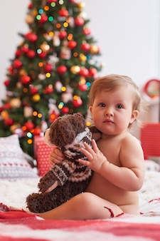 Baby auf dem hintergrund des weihnachtsbaumes mit einem spielzeug