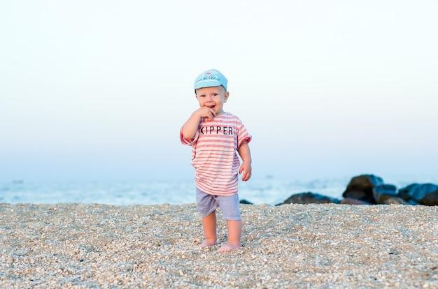 Baby auf dem sand nahe meer im blauen hut und in der gestreiften kleidung. sommer-konzept. erholsamer urlaub, strandurlaub.
