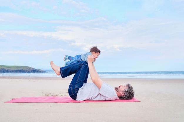 Baby auf dem schoß ihres vaters beim yoga am strand