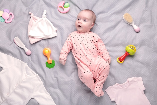 Baby auf weißem hintergrund mit kleidung, toilettenartikeln, spielzeug und gesundheitszubehör. wunschliste oder einkaufsübersicht für schwangerschaft und babyparty.