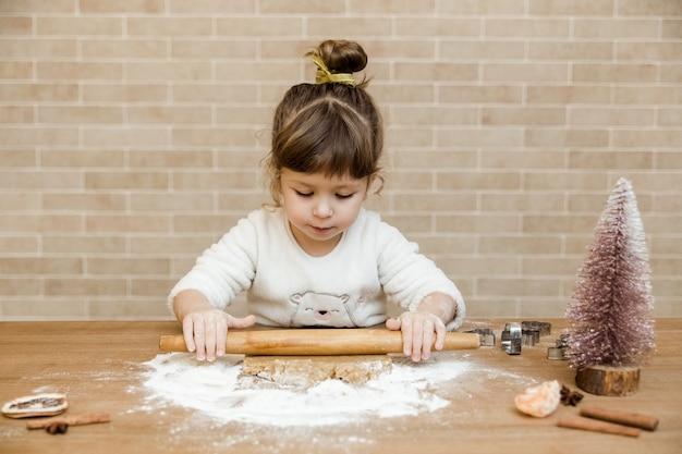 Baby bereitet lebkuchen in der küche vor. mädchen mit nudelholz, teig und mehl