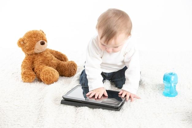 Baby berührt den bildschirm einer tablette mit einem teddybär an der seite und einem behälter mit griffen zum trinken.