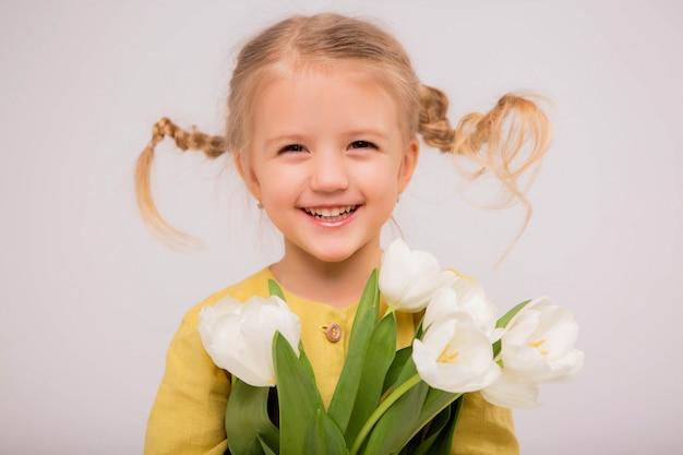 Baby blondine mit einem strauß tulpen auf hellem hintergrund