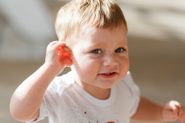 Baby boy hört zu, eine hand an sein ohr zu legen.