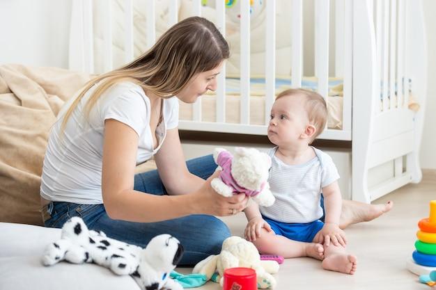 Baby boy spielt auf dem boden im wohnzimmer mit mutter