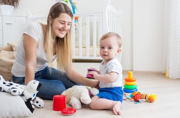 Baby boy spielt mit spielzeug-handy auf dem boden im wohnzimmer
