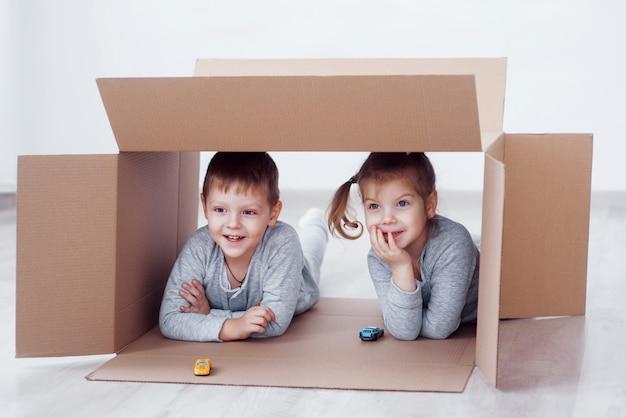 Baby bruder und kind schwester spielen in pappkartons im kinderzimmer