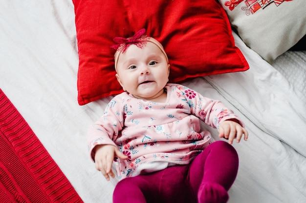 Baby, das auf bett mit kissen im schlafzimmer liegt. fröhliche weihnachten. draufsicht, flatlay. das konzept des familienurlaubs. nahansicht.