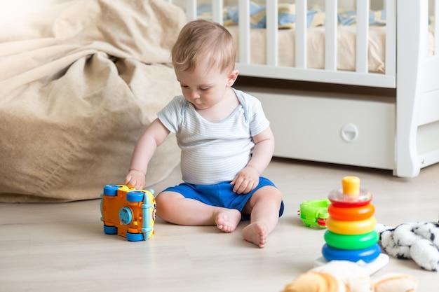 Baby, das auf dem boden mit buntem spielzeugauto spielt