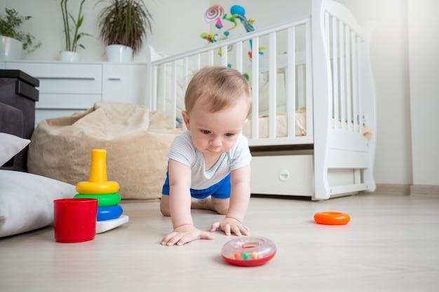 Baby, das auf dem boden mit bunten ringen vom spielzeugpyramide-turm spielt