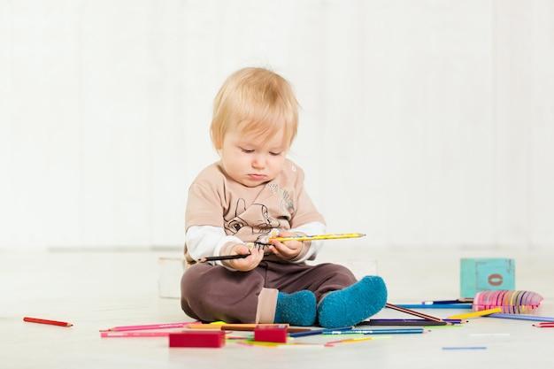 Baby, das auf dem boden mit spielwaren spielt
