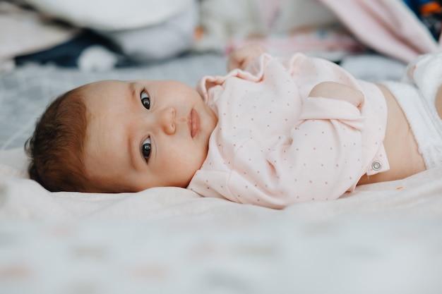 Baby, das auf dem rücken auf dem bett in einem hellen schlafzimmer liegt, gekleidet in ein leichtes sommerkleid. ruhiges baby baby 3 monate alt. speicherplatz kopieren