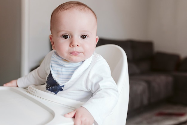 Baby, das auf der essfertigen säuglingsnahrung des stuhls sitzt. zuhause, drinnen