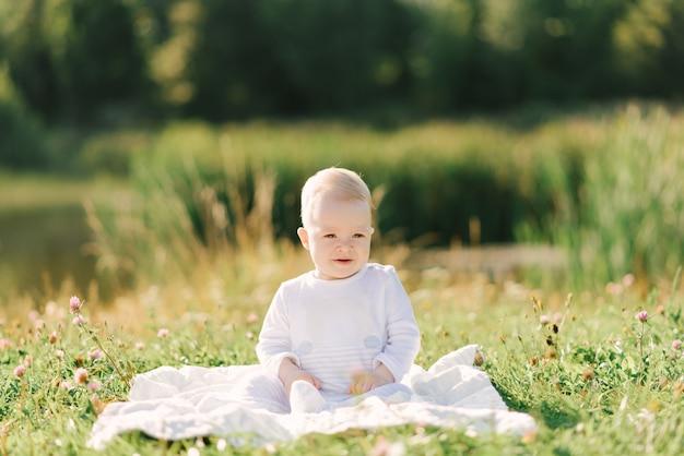 Baby, das auf einem plaid auf natur in einem hellen bodysuit sitzt