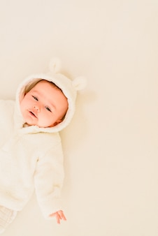 Baby, das auf einem weißen bett, entzückende schauende kamera liegt.