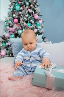 Baby, das auf einer pelzdecke mit kissen und geschenken mit weihnachtsbaum sitzt