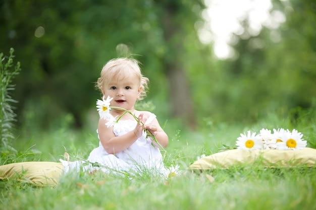 Baby, das auf grünem gras sitzt