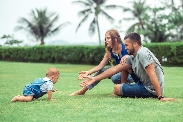 Baby, das auf grünem rasen während des spaziergangs mit ihren eltern kriecht