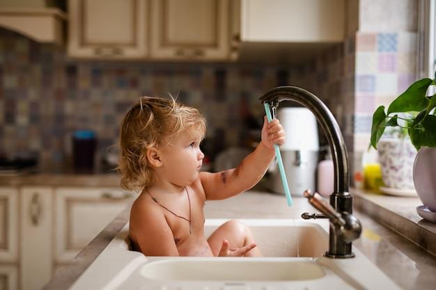 Baby, das bad im spülbecken nimmt. kind, das mit wasser in der sonnigen küche mit fenster spielt.