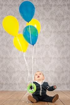 Baby, das bündel ballone hält