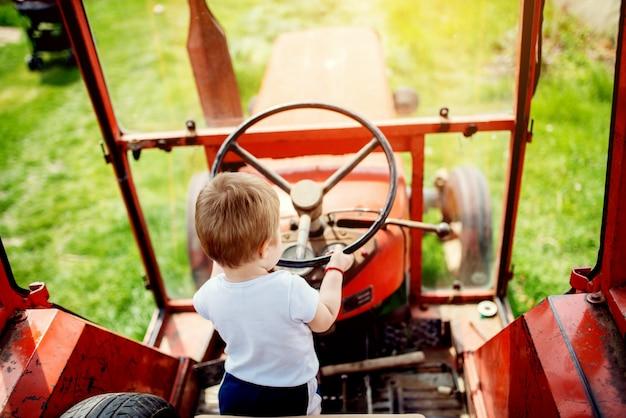 Baby, das ein lenkrad des traktors hält.