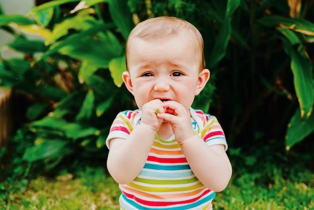 Baby, das eine blume verschlingt, die sich aus dem garten gepflückt hat, um ihren geschmack zu schmecken.