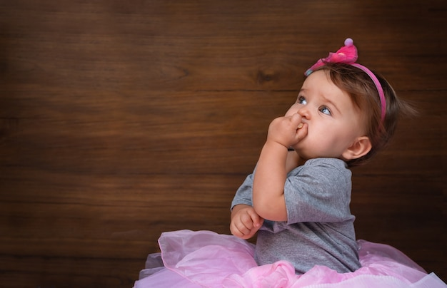 Baby, das einen keks auf einem hölzernen hintergrund isst. kind im rosa kleid auf holzhintergrund