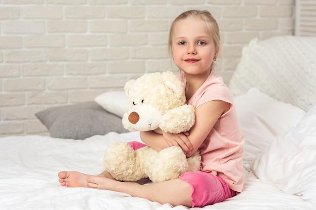 Baby, das einen teddybären umarmt