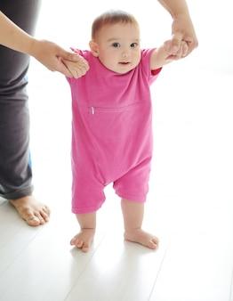 Baby, das erste schritte mit mutterhilfe auf weißem hintergrund unternimmt