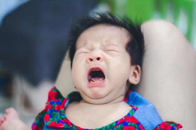 Baby, das hungrig nach mutter auf dem knie der tante schreit