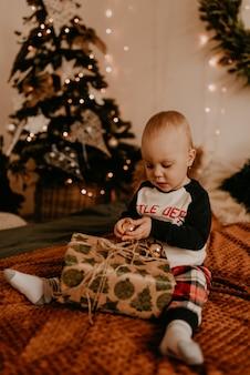 Baby, das im schlafanzug auf dem bett im schlafzimmer sitzt und ein geschenk öffnet. weihnachtsmorgen. neujahrsausstattung. valentinstag feier