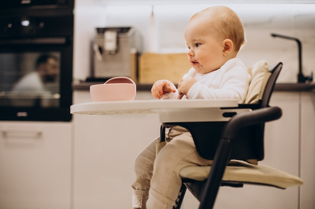 Baby, das im stuhl sitzt und brei isst