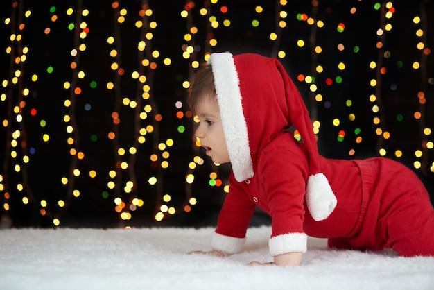 Baby, das in der weihnachtsdekoration als santa boke lichter auf dunklem hintergrund gekleidet aufwirft