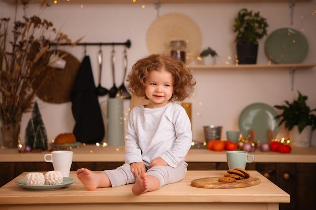 Baby, das in der weihnachtsküche auf tabelle sitzt
