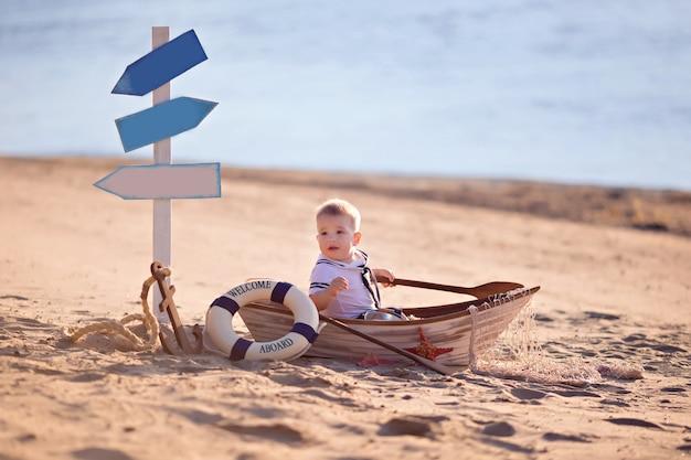 Baby, das in einem boot an einem strand sitzt