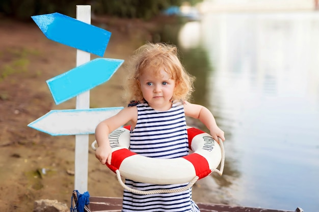 Baby, das in einem boot sitzt, als seemann verkleidet, an einem sandstrand mit muscheln am meer