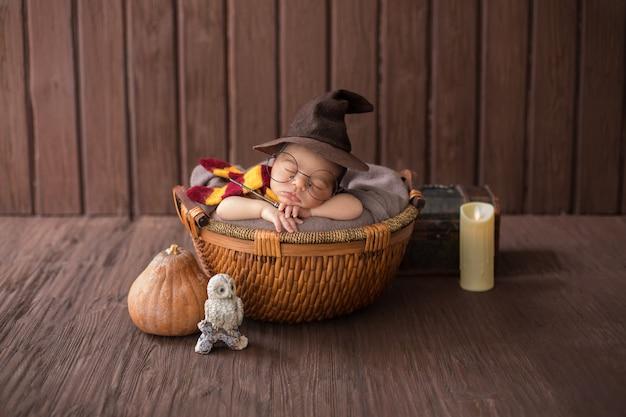 Baby, das innerhalb des kleinen korbs mit lustigem zaubererkostüm liegt