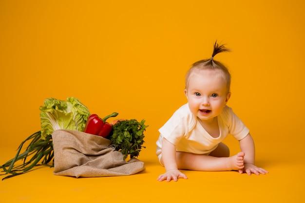 Baby, das mit beutel des gemüses auf orange sitzt