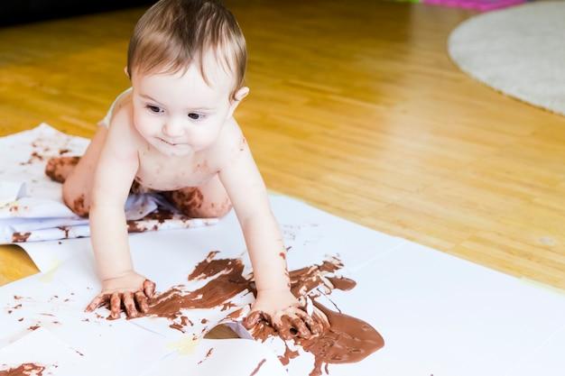 Baby, das mit den händen mit schokolade malt