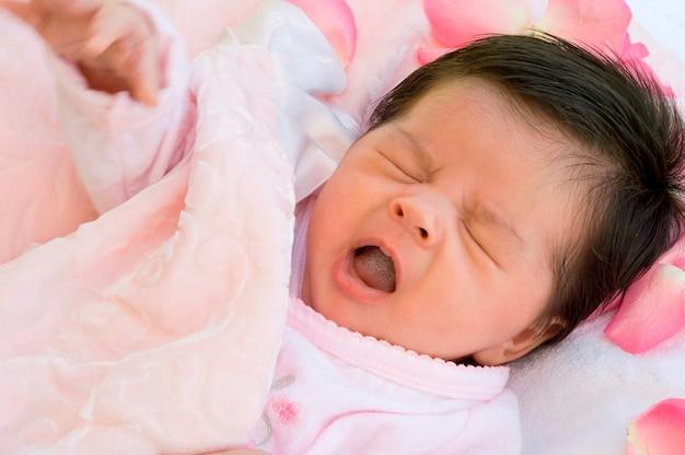 Baby, das mit den rosen-blumenblättern gähnt