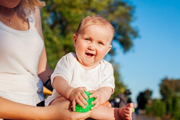 Baby, das mit den spielwaren sitzen auf den knien ihrer mutter im sommerpark spielt.
