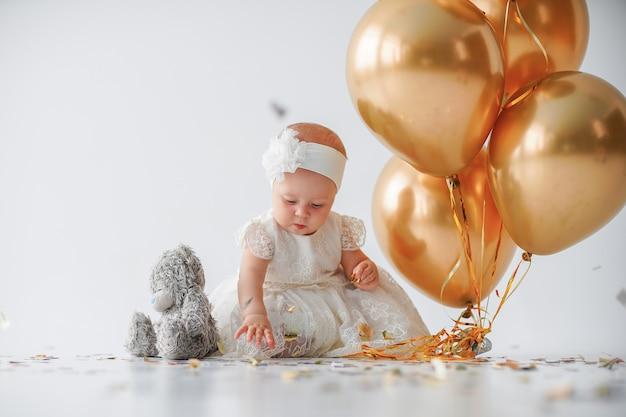 Baby, das mit einem bündel goldener luftballons sitzt