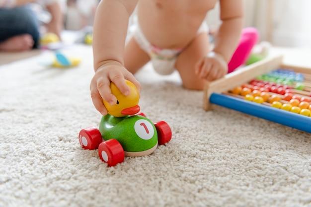 Baby, das mit einem hölzernen auto spielt