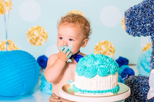 Baby, das mit einem kuchen während der kuchen zerschmettert geburtstagsfeier spielt