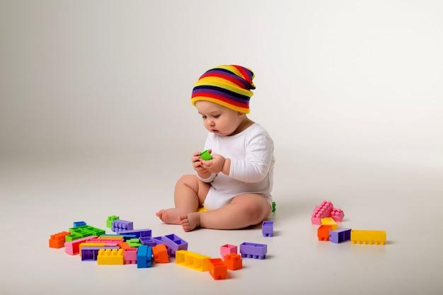 Baby, das mit einem mehrfarbigen konstrukteur auf einer weißen wand spielt
