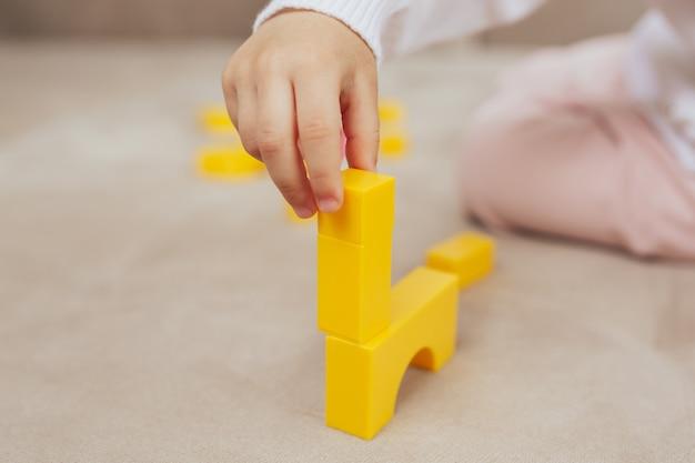 Baby, das mit gelben spielzeugblöcken spielt und gebäude gebaut wird