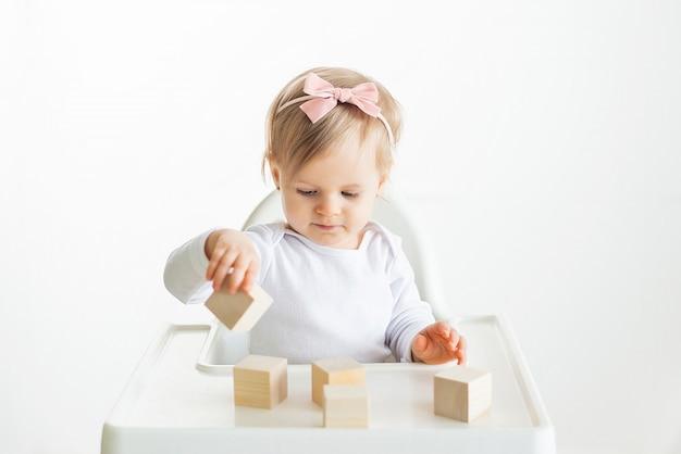 Baby, das mit holzwürfeln durch linke hand spielt. spielendes kleinkind lokalisiert auf weißem hintergrund. spiele für kinder, vorschulerziehung. nahaufnahme, selektiver fokus