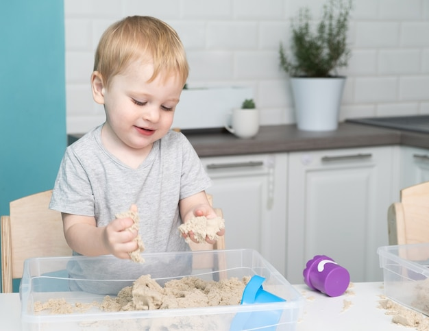 Baby, das mit kinetischem sand zu hause spielt.
